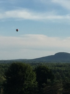 a hot air baloon floats over a mountian